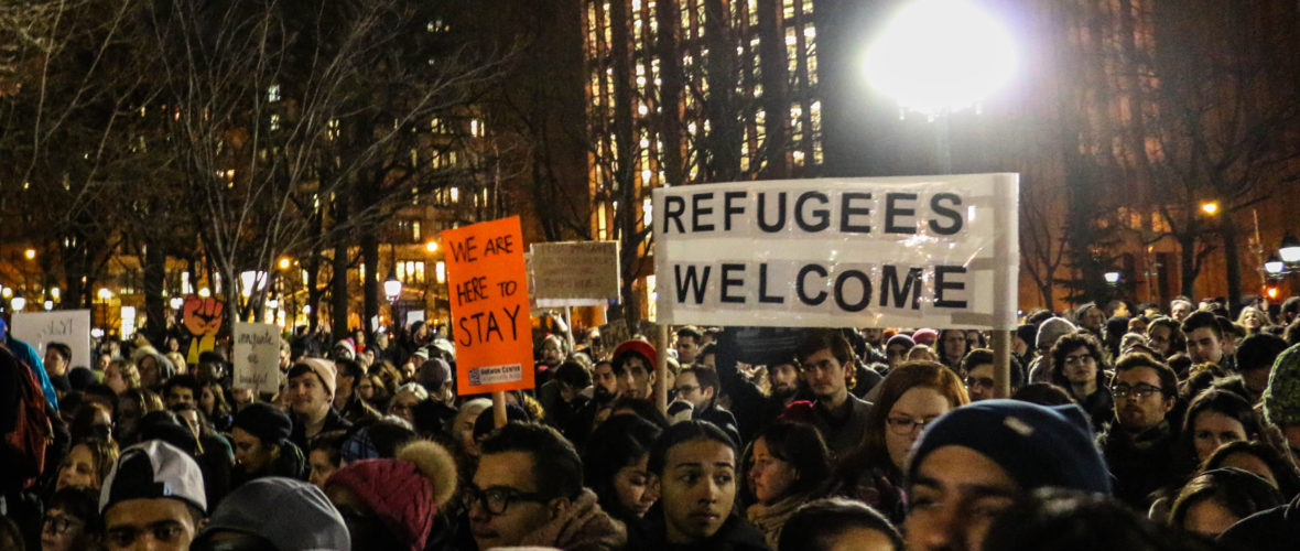 """Crowd protests Trump immigration policies, signs read: """"Refugees Welcome"""" and """"We are Here to Stay"""""""